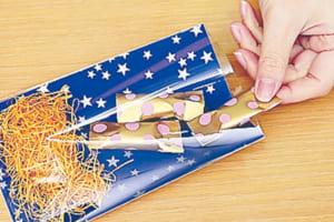 なるべく隙間ができないようにお菓子を詰めて折り曲げ、マスキングテープなどで留める