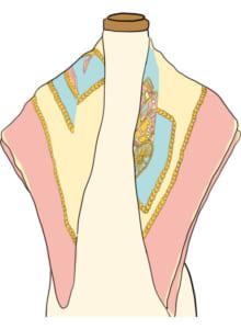 スカーフを対角線上で半分に折り、肩に羽織る