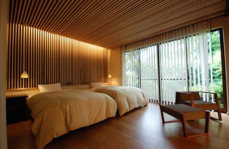 同社がリニューアルを手掛けた、南阿蘇村の温泉旅館の客室。木と間接照明の陰影が雰囲気抜群