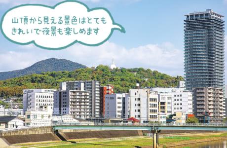 山頂にある白い仏舎利塔が目印。春は桜の名所としても有名です。奥は金峰山