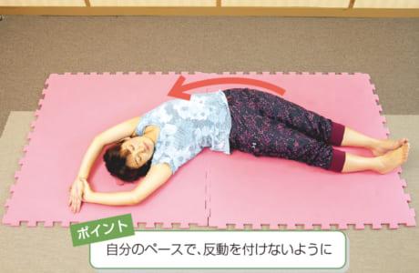 右手で左手を引きながら体を傾ける。同時に、そろえた両足を右方向に動かし、弓なりになる。反対側も行う。