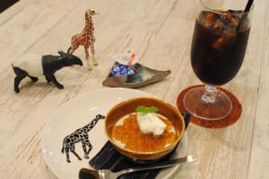 """""""本日のデザート""""の「ほうじ茶のパンナコッタ」350円(手前)、こだわりの豆を使用した「水出しアイスコーヒー」480円(右奥)。お皿のキリンのイラストは、堀さんが描いたもの"""