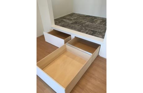 リビングの一角に設けられた小上がりの部屋。収納スペースも設けられています