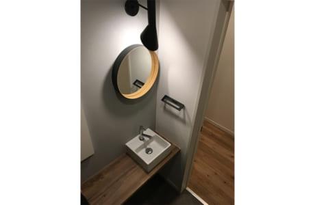 丸い鏡が設置されたおしゃれなトイレ。落ち着いた雰囲気です