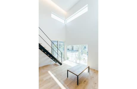 吹き抜けには大きな窓があり、明るく開放的に。窓枠が額縁のように外の景観を切り取ります