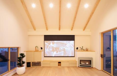 (施工例)ホームシアターを備えたリビング。暖炉がくつろぎの空間を演出