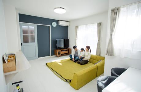 住居スペースは床と壁、天井を白で統一。一面だけ施されたネイビーのクロスがアクセントに
