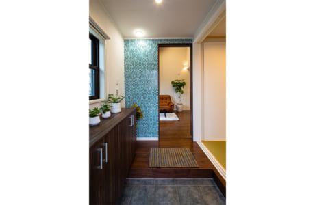 効率よくレイアウトされた玄関。グリーンのタイルがインテリアのアクセントに