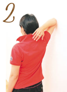 伸ばした方の腕は、肘(ひじ)を曲げて手を肩甲骨の方に持っていきながら、体側を少しずつ壁につけていき8秒間止める。同じ動きを左右3セットずつ行う。