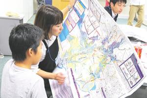 ハザードマップを見ながら自分の住む地域の危険度をチェックする親子