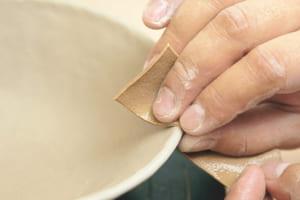 口べりに、水につけたなめし皮を当て、縁を整えます。これで成形が完了