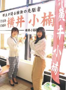 秋津まちづくりセンター内に掲示されている横断幕とのぼりの前でポーズを取る探検隊の2人