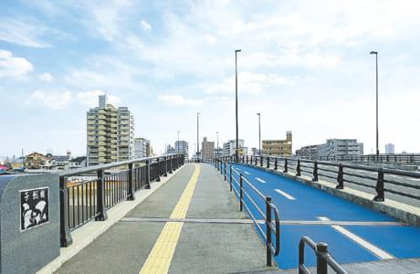橋の両側に設けられた青い舗装の自転車専用道。これがあると歩行者も安心!