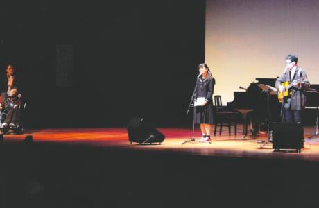 障がいのある人や水俣病の被害を受けた人が思いをつづった詩に曲を付けて歌う「もやい音楽祭」で、障がい者の介添えをする飯川さん(写真左)